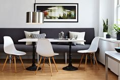 The dining area's custom-made banquette, which is upholstered in a slate Architex fabric, is brightened with white accents, including three molded plastic Eames-style chairs. Ramchandani commissioned the laminate-top dining table from West Coast Industries.