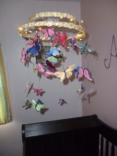 DIY butterfly nightlight mobile. I've been looking for a nightlight my daughter can't reach and I don't have to unplug and hide each morning so she doesn't try to unplug it herself. I used a strand of LED lights wound around this homemade mobile. It's really pretty at night.