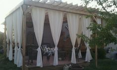 Drapes on Pergola with misting system!   I used shower curtains, they hold up to rain/weather better and have holes at the top for easy hanging!