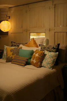 Absolutely love this salvaged wood door headboard and those paper lantern sconces!