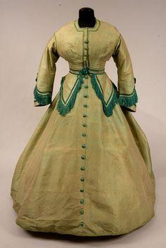 Green silk brocade dress with darker green fringe trim, c. 1860's.