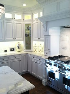gorgeous cabinetry, lights in upper glass cabinets, MARBLE.