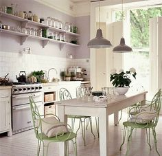 French style kitchen painted in a pale lavender and accented with vintage green iron chairs