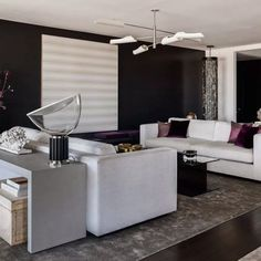 The contrasting deep walls and white surfaces welcome more space to this living room.