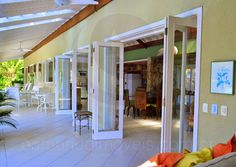 Portas deslizantes conectam todos os ambientes com o alpendre, decorado por móveis em madeira e fibra natural.