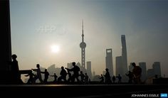 CHINA, Shanghai: Taichi practitioners practice their martial art at sunrise in front of the financial district of Lujiazui in Shanghai on  April 1, 2015. AFP PHOTO / JOHANNES EISELE