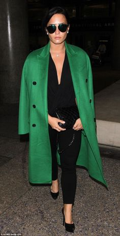 Not happy? Demi Lovato, 24, looked glum as she arrived back in Los Angeles from Dubai wearing an eye-catching bright green coat and sunglasses