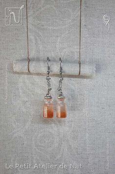 [ Fait-Main ] avec des crochets d'oreille, des anneaux et des chaînes en acier inox, de minuscules perles métalliques, des anneaux en fil aluminium (Ø2), une petite bouteille en verre remplie de résine (fait-main.) La résine danse entre translucide et couleur cuivre, parsemée de fines paillettes de mica, ces petites bouteilles ou fioles sont magiques : si l'on y croit, pourquoi pas ! Parce qu'elles sont nées de la fantaisie de leur créatrice (Nat) grande fan de poussières d'ailes de fées et…