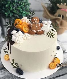 A festive gingerbread Christmas cake. This simple base white cake gathers points with its lovely decoration of gingerbread man, white meringues, snowflakes, berries and tangerines. Christmas Cake Designs, Christmas Cake Decorations, Holiday Cakes, Christmas Desserts, Christmas Treats, Christmas Baking, Mini Cakes, Cupcake Cakes, Winter Torte