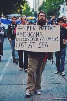 """Happy Indigenous Peoples Day, Seattle!"" I appreciate the opposing view given by this sign holder, referencing the very obvious fact that, you cannot discover a country which has already been discovered, populated, and cultured, and a lot more natives spoke English than anyone cares to recall."
