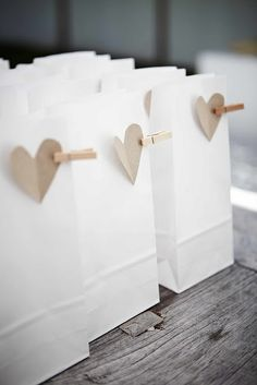 Super-simple yet so cute | Wedding favours. All you need is white paper bag, heart punch and craft mini pegs. So simple yet so chic. Think that with pastel shade bags and a white heart this would also look amazing!