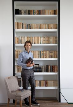 Pierre Yovanovitch stands in front of his collection of midcentury Cartonnages Bonet-Prassinos.