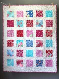 This modern baby girl quilt is completed and ready to ship to you! This baby quilt features a beautiful girly color palette of pinks, reds, and