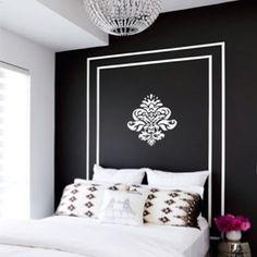 Faux headboard, metallic nightstand, crystal chandelier, and I love the walls.
