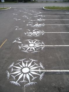 diy & go graffiti a parking lot, wind blowing dandelion seeds into the air.
