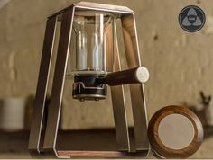 """Trinity ONE: Mark Folker's stainless steel and black walnut timber finish coffee device is advertised """"to be on display, not hidden away"""", a multi-technique preparation station capable of pour over, air pressure, and cold brew so users can experience the taste of beans in numerous ways."""