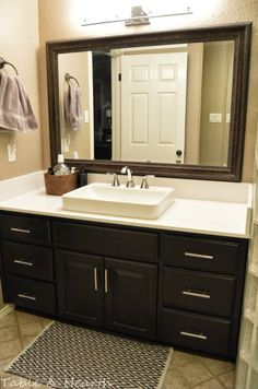 Our DIY master bathroom update featuring white quartz countertops, refinished cabinets, and a large Kohler sink with chrome faucet.