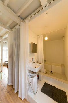 洗面、バスルームはドアを取り付けずカーテンで仕切る。白一色の空間がどこか幻想的。