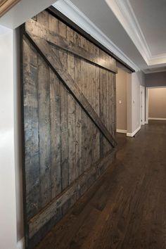 Custom oversized sliding barn door serving as optional divider for a game & media room