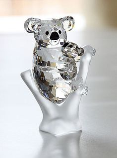 Swarovski code numbers: 955 423 / 955423 / 9100 000 121 The world's cutest hug - crystallized. This mother koala in fully faceted clear crystal embraces her little cub in Golden Teak crystal as she sits on a matte crystal tree trunk. The nose and eyes of the koalas are in Jet crystal, contrasting sharply with their bodies. A cuddly pair that's hard to resist. Part of the Rare Encounters group. Size: 5.1 x 7.7 cm Designer: Peter Heidegger Introduced: 2009 Retired: 2013