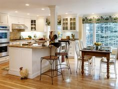 Country kitchen, large window, island bench (without that pillar!), even a rooster!  Like to have a small family lunch table nearby, want a wall oven, need to have kickboards, not sold on glass fronted cupboards