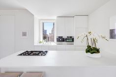 This modern New York City kitchen features all-white surfaces and cabinetry, where views of the skyline steal the show. #kitchen #modernkitchen #whitekitchen