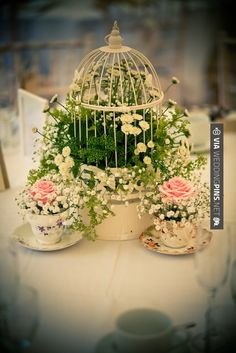 Lovely display of flora and fauna with birdcage and teacups