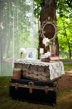 Antique trunks create a vintage-themed display table for an outdoor wedding. #VintageWedding #WeddingDecor