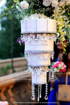 Chandelier Wedding Cake - Four Tier Chandelier Wedding Cake hanging upside down on a stand. The cake was decorated with Sugar Flowers, Silver Studded Ribbons & Crystals.