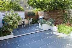Outdoor dining on slate patio. Would swap the slate in the main part of the garden to grass and I would then have the garden I want! Wonderful!