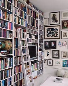 office library & picture wall. I love the cleanness of the white but with the jumbled colours of the books and the linear pattern of the pictures over that.