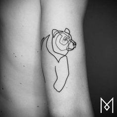 Continuous line bear tattoo on the back of the right arm.