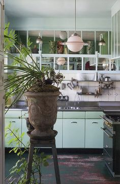 kitchen with mint cabinets and green house plants and pendant lamp via greenterior / sfgirlbybay