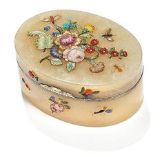 A German gold mounted cloudy quartz snuff-box, oval, lid and sides applied with flowers, leaves and insects sculpted out of various coloured hardstones, legs, antennae and details of the insects engraved and blackened. Attributed to Friedrich Ludwig Hoffmann, probably Berlin, second half of the 18th century. L. 8.4 cm. H. 3.8 cm.