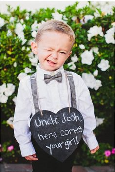 Ring bearer with a chalkboard sign, so cute!