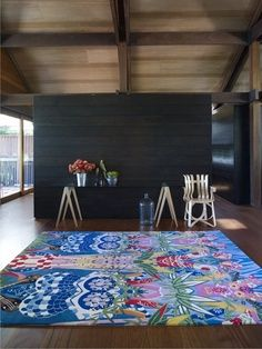 A simple half wall divides this open space and that delightful rug, makes a huge design statement!