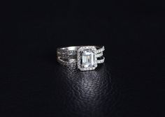 14KW Emerald Cut Diamond Center with Halo and Three Stand Diamond Band on Sides.