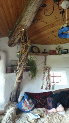 The interior of Christian and Louise's cob cottage. Colin of Mud and Wood helped build the roof, including installing the ridge beam trunk with supporting branch.