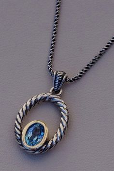 Sterling Silver & Yellow Gold Oval Pendant with Swiss Blue Topaz on an 18 Inch Sterling Silver Chain available at J. Schrecker Jewelry.