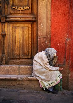 Elderly woman, bent over, taking a rest from her walk. San Miguel de Allende, Mexico. Tomas Castelazo