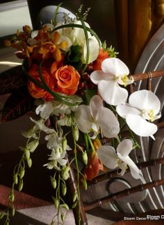 Flowing bridal bouquet with orange roses, white calla lilies, orange calla lilies, white phalaenopsis orchids, white dendrobium orchids, orange dendrobium orchids, red hypericum berries and lily grass.