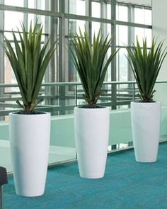 Group Of Three Faux Plants In Large Pots Against Rock Wall
