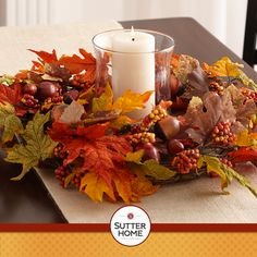 Dress up your dining table for #Thanksgiving by creating a centerpiece out of a fall wreath laid flat with large hurricane vase with a candle at its center.