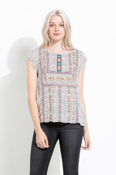 The geometric embroidery on the bohemian print adds a colorful contrast! Great with jeans for a casual chic look or tucked into a skirt for work.