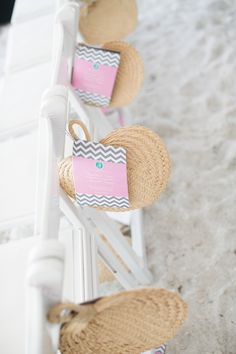 beach wedding aisle decor idea ...fan's & programs on the back of chair's. . Great idea.  Cute and sensible.