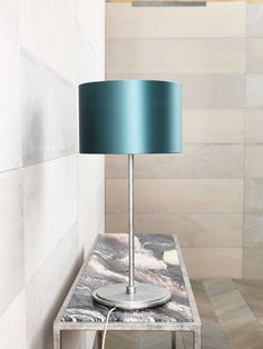 A Madison table lamp with an Antique Silver finish on a Siena console table with Rosso Luna marble top.