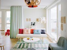 déco salon moderne - canapé droit blanc, coussins capitonnés colorés, tapis rustique et table basse ronde en blanc