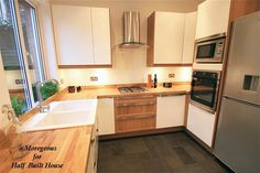 Exeter : White gloss kitchen with oak work surfaces, drawer fronts and end panels. Dark slate grey tiled floor.