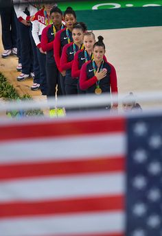 #RIO2016 The gold medalwinning US women's gymnastics team watches the nation's flag raised during the medal ceremony following the team competition on Tuesday...