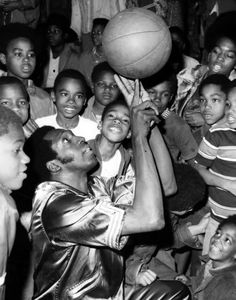 cf6cf653393c Meadowlark Lemon of the Harlem Globetrotters captivates a young crowd with  his Basketball trickery. I